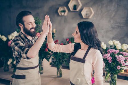 Close up side profile photo partners she her lady him his he guy clapping arms amazed excited earn big order money compositions bunches fresh flowers owners wear aprons small flower shop room indoors