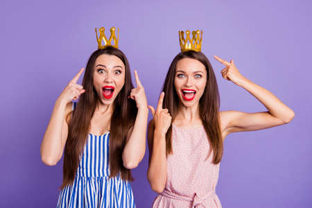 Close up portrait two people amazing beautiful she her models ladies indicate fingers power status gold crowns head look wear summer colorful dresses isolated purple violet bright background Фото со стока