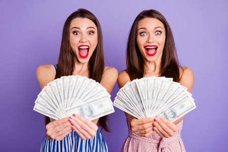 Close up photo two people beautiful she her models ladies raise money hands arms hold buy buyer pay payment fan usa bucks yell wealthy wear colorful dresses isolated purple violet background