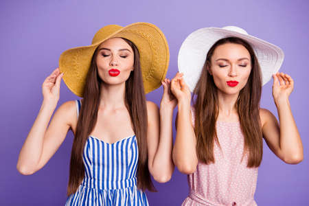 Close up photo two beautiful funky she her models classy ladies hold hands sunny weather go walk send air kisses boyfriends coquettish wear sun hats summer dresses isolated purple violet background Reklamní fotografie