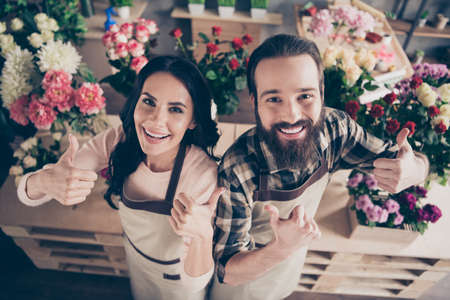 Close up top above high angle photo two people she her wife lady him his he husband guy advice buy buyer service thumbs up compositions bunches fresh flowers owners small flower shop room indoors