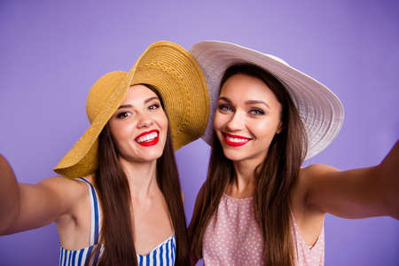 Close up photo two beautiful funny funky she her models ladies perfect sunny weather coquettish mood make take selfies red lips toothy wear sun hats summer dresses isolated purple violet background