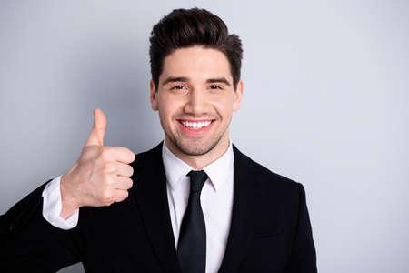 Close-up foto geweldig hij hem zijn macho knappe hand arm duim omhoog adviseren kopen koper nieuw getest geweldig product dragen wit overhemd zwart pak jasje stropdas formele kleding geïsoleerd heldere grijze achtergrond
