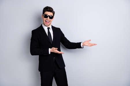 Stilvolles Produktkonzept. Porträt gutaussehender intelligenter Immobilienmakler beraten Sie sich, geben Sie Informationen und schlagen Sie aufgeregte Inhalte vor, genießen Sie isolierte graue Hintergrundspezifikationen Brillen-Outfit