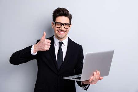 Ritratto del suo lui bello imponente attraente allegro ragazzo positivo e-commerce borsa che mostra thumbup leader esecutivo esperto agente di sviluppo broker vendite isolate su sfondo grigio chiaro