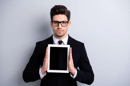 Portrait of elegant classy attractive guy showing holding in hands black display new digital ebook isolated over light gray background