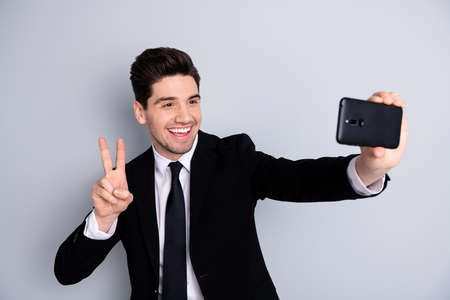 Portrait of funny ceo feel excited have rest break pause make v-signs take photos use user gadgets blog blogging wear black modern jackets isolated on grey background