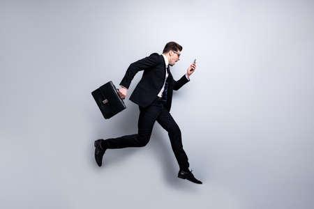 Voller Körpergröße Profilseitenansicht Porträt seines schönen, eleganten, attraktiven nervösen besorgten Kerls, der in den Händen Diplomatenzelle mit weißem Kragen Rush Hour Karrierewachstum einzeln auf hellgrauem Hintergrund trägt