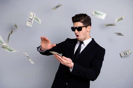Ritratto del suo bel contenuto attraente ragazzo arrogante top sales manager finanziere banchiere economista direttore gettando via il credito della lotteria di cambio valuta isolato su sfondo grigio chiaro
