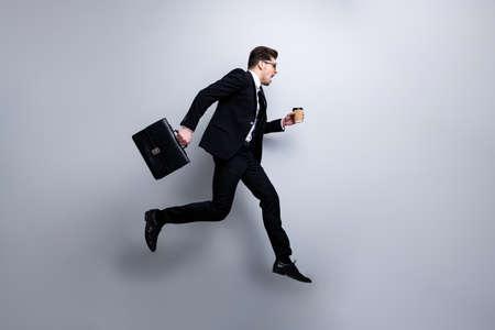 Ganzkörpergröße Profilseitenansicht Porträt eines netten, attraktiven, besorgten Kerls, der in den Händen Diplomat Latte White Collar Rush Hour Karrierewachstum Arbeitsplatz einzeln auf hellgrauem Hintergrund trägt Standard-Bild