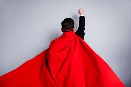 Nahaufnahme von hinten hinter dem Ansichtsfoto, das den Gesichtsausdruck verbirgt, er hat seine Mannfaust hochgehoben, verwenden Sie die Supermacht, tragen Sie einen roten langen Mantel, der den Windsicherheitsschutz für das menschliche Rassenkonzept isoliert grauer Hintergrund erhöht