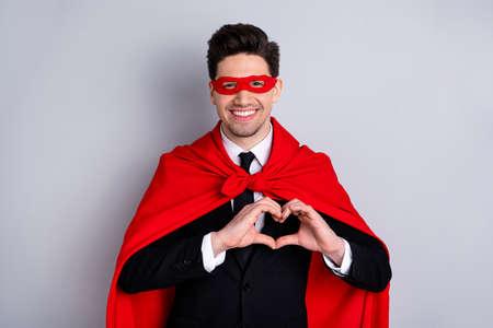 Nahaufnahme seines hübschen, attraktiven, fröhlichen, fröhlichen Kerls, der ein helles, lebendiges Super-Look-Outfit-Accessoire trägt, das Gestenhandfingerherz einzeln auf hellgrauem Hintergrund zeigt