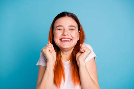 Portrait of cute funny funky teen teenager raise fists close eyes interested plead wait expect want feel content satisfied glad present gift dressed spring clothing isolated blue background
