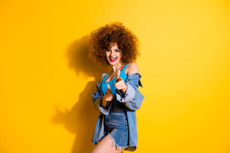 Portrait of her she nice cute lovely charming attractive winsome girlish cheerful wavy-haired girl pointing two forefingers at you isolated over bright vivid shine yellow background