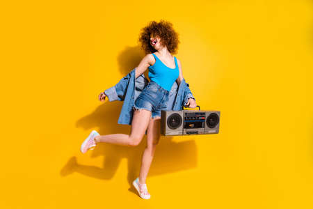 Full length body size photo beautiful she her lady wavy styling curls old-fashioned tape recorder dancing excited wear specs casual jeans denim shirt shorts tank top clothes isolated yellow background