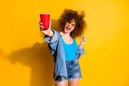 Close up photo beautiful she her lady wavy styling curls festive mood clubber little drunk beverage hand wear specs casual jeans denim shirt shorts tank top outfit clothes isolated yellow background