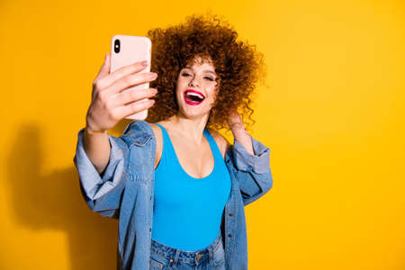 Portrait of her she nice lovely glamorous charming attractive cheerful cheery glad wavy-haired girl taking making selfie dream isolated over bright vivid shine yellow background