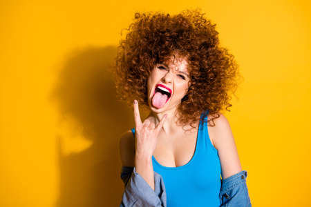 Close-up portrait of her she nice charming crazy lovely attractive cheerful cheery funny wavy-haired girl showing rocknroll sign symbol isolated over bright vivid shine yellow background