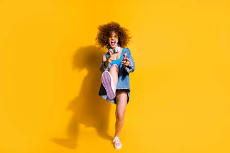 Full length body size photo funky funny  lady wavy styling clubber strange moves fingers direct wear ear flaps specs casual jeans denim shirt shorts tank top clothes isolated yellow background