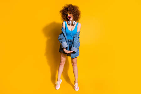Full length body size photo jumping funky funny   lady wavy styling curls clubber amazed excited wear ear flaps specs casual jeans denim shirt shorts tank top clothes isolated yellow background