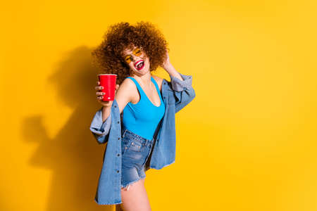 Close up side profile photo beautiful  lady wavy styling curls festive clubber drunk beverage hand wear specs casual jeans denim shirt shorts tank top outfit clothes isolated yellow background