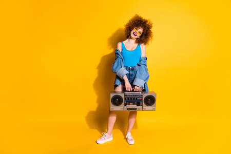Full length body size photo beautiful pretty she her lady wavy styling curls old-fashioned tape recorder wear specs casual jeans denim shirt shorts tank top outfit clothes isolated yellow background