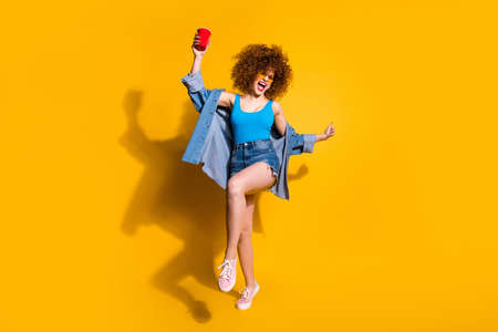 Full length body size photo funny funky she her lady wavy styling curls sing song beverage little drunk hang out wear specs casual jeans denim shirt shorts tank top clothes isolated yellow background