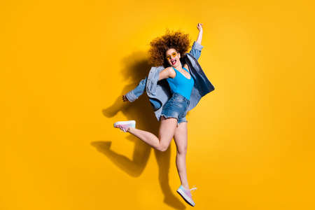 Full length side profile body size photo funny funky she her lady styling curls jumping high having fun excited wear specs casual jeans denim shirt shorts tank top clothes isolated yellow background Standard-Bild