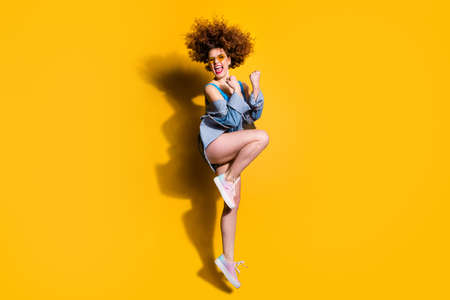 Full length side profile body size photo funny funky she her lady wavy styling curls jump high great win wear specs casual jeans denim shirt shorts tank top clothes isolated yellow bright background Stock Photo