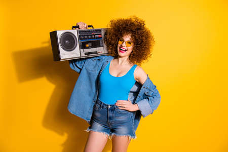 Close up photo beautiful lady wavy fluffy styling curls hands old-fashioned tape recorder wear casual jeans denim shirt shorts blue tank top outfit clothes isolated yellow bright background Banque d'images