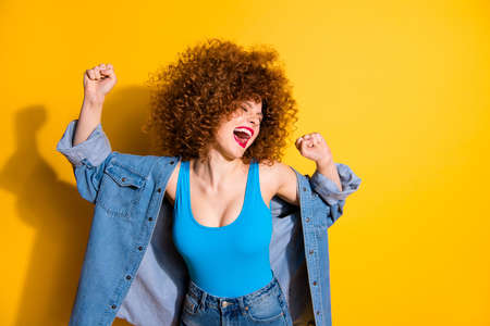 Close up photo beautiful amazing lady wavy fluffy curls excited hands arms raised I am best wear casual jeans denim shirt blue tank top outfit clothes isolated yellow bright background