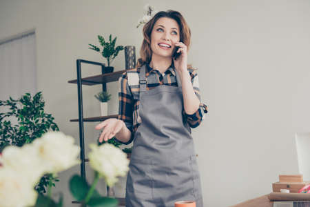 Portrait positive cheerful satisfied excited lady vendor free time dialogue use modern technology marketing share information sales discounts wavy curly hairstyle trendy stylish shirt plaid indoors