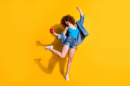フルレングスのボディサイズの写真面白いファンキー彼女の女性の波状のスタイリングカールは叫び声小さな酔っぱらいのハングアウトスを着用してスペックカジュアルジーンズデニムシャツショートパンツタンクトップ服孤立黄色の背景