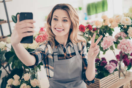 Close up photo beautiful she her lady blogger hands arms telephone make take selfies show v-sign various option retail seller offering buy buyer big choice choose owner small flower shop room indoors Stock fotó