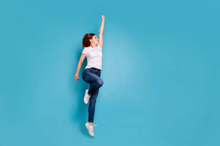 Full length body size profile side view portrait of nice attractive cheerful strong girl in white tshirt active mood life lifestyle raising hand arm up isolated on bright vivid shine blue background