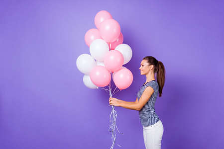 Profile side view portrait of her she nice-looking attractive lovely charming cute cheerful cheery girl holding in hands helium balls isolated over violet purple vivid shine bright background