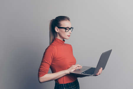 Profilseitenansicht Porträt von ihr sie schöne schöne attraktive professionelle intelligente Mädchenbrille hält Netbook in der Hand und schreibt neue Artikelgeschichte einzeln auf grauem Pastellhintergrund