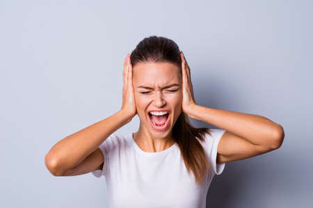 Close up photo amazing beautiful she her lady not fear situation epic fail bad mood yelling loud eyes closed hide ears terrible noise wear casual white t-shirt clothes isolated grey background 版權商用圖片