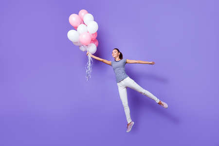 Full length body size view portrait of her she nice attractive lovely fashionable cheerful cheery girl having fun flying with helium balls isolated over violet purple vivid shine bright background Stock Photo