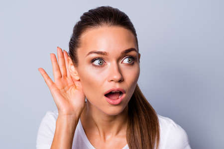 Close up photo beautiful amazing funky her she lady arm hand palm near ear try to hear news novelty open mouth chatterbox bad silly person wear casual white t-shirt isolated grey background
