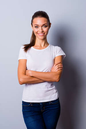 Vertical close up photo beautiful she her lady hands arms crossed self-confident easy-going reliable business person wondered look wear jeans denim casual white t-shirt isolated grey background 版權商用圖片