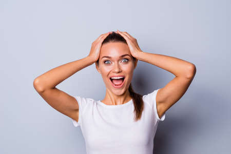 Close up photo beautiful amazing pretty yelling loud she her lady perfect appearance arms raised touch hold head forehead open mouth not believe eyes wear casual white t-shirt isolated grey background