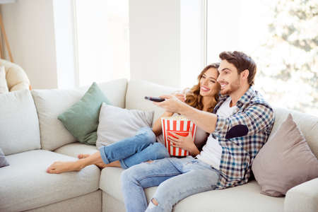 Profile side view of his he her she two person nice attractive charming cheerful guy lady sitting on divan watching new drama comedy in light white style interior living room hotel house indoors