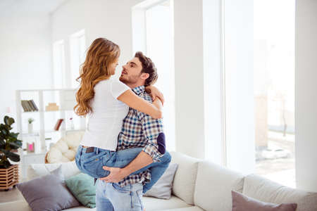 Nice-looking winsome attractive lovely lovable charming guy wavy-haired lady spending free time honey moon harmony idyllic in light white style interior living room house Banque d'images - 123313699