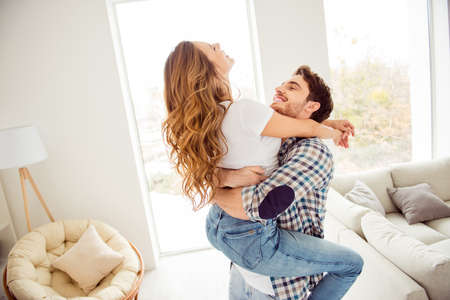 Close up side profile photo pair beautiful he him his macho she her lady just married honeymoon playful childish hold hands round circle movement motion apartments flat bright room indoors