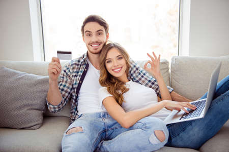 Portrait of her she his he two person nice attractive lovely cheerful cheery guy lady sitting on divan showing ok-sigm advert ad advice in light white style interior room house indoors Фото со стока - 123313847