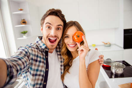 Close up photo pair beautiful amazing funky pair he him his macho she her lady hide eye fresh tomato just married honeymoon overjoyed make take selfies bonding apartments flat bright kitchen indoors