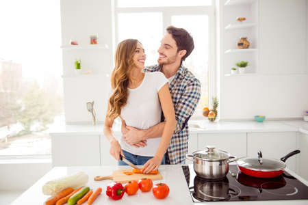 Close up photo pair beautiful he him his macho guy distracting hold waist hands she her toothy lady just married honeymoon overjoyed make breakfast dish bonding apartments flat bright kitchen indoors Banco de Imagens