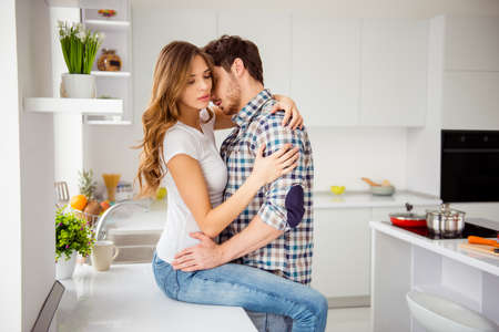 Close up side profile photo pair beautiful he him his macho she her lady married eyes closed hold each other hands bonding hugging touch desire sit table apartments flat bright kitchen room indoors