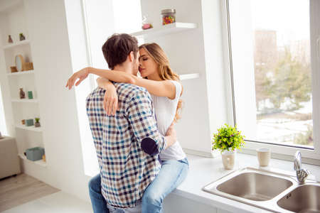 Close up photo pair beautiful he him his macho she her lady just married overjoyed hold each other hands bonding hugging touch lips going kiss desire apartments flat bright kitchen room indoors Reklamní fotografie